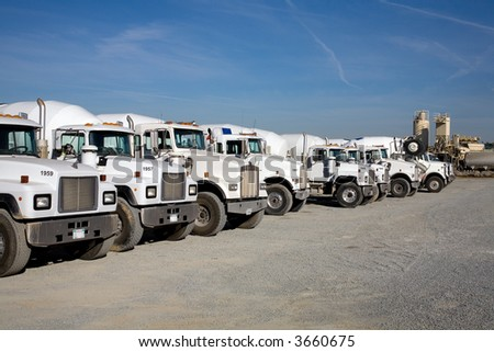 Transit mix concrete trucks ready to deliver their loads to construction job site - stock photo