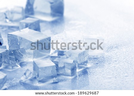 translucent ice cubes and water drop on light blue background - stock photo