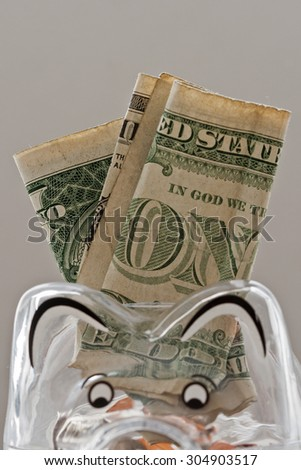 Translucent piggy bank filled with dollar notes and coins  - stock photo