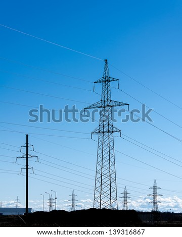 Transmission power towers at sunset - stock photo