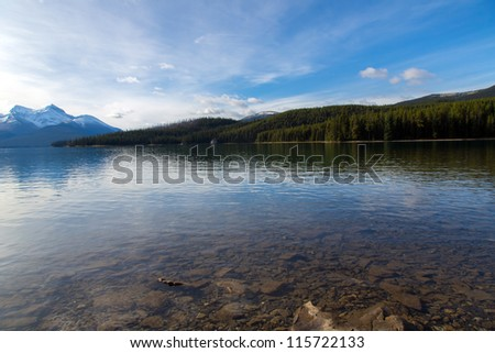 Transparent clear lake with mountains and forest on background - stock photo