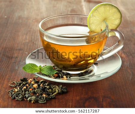 Transparent cup of green tea with lime on wooden background - stock photo