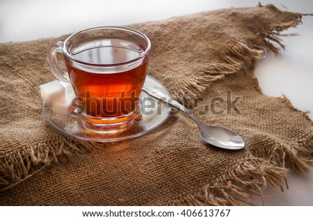 Transparent Cup with tea and a spoon. - stock photo