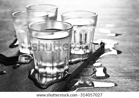 Transparent drink in the sweaty glass. Black-and-white image. Selective focus. - stock photo