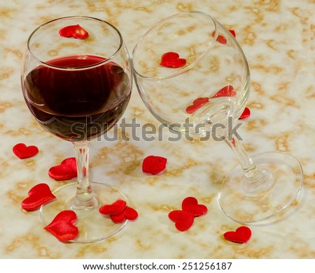 Transparent glasses with red wine and textile red valentine hearts, old paper background, close up. - stock photo