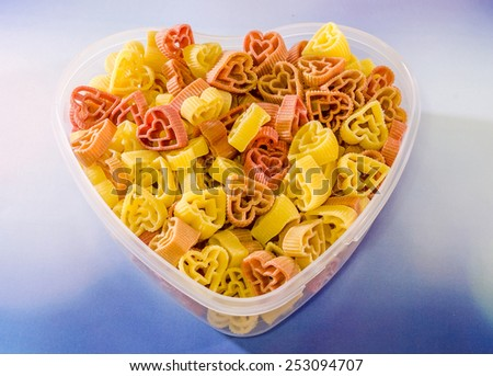 Transparent heart shape vase (bowl) filled with colored (red and yellow) heart shape pasta, red bokeh background, close up - stock photo
