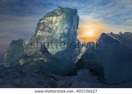 Transparent ice on sunset sky background. - stock photo