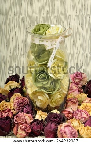Transparent of glass vase with flowers roses and dried in the herbarium flowers in still life. - stock photo