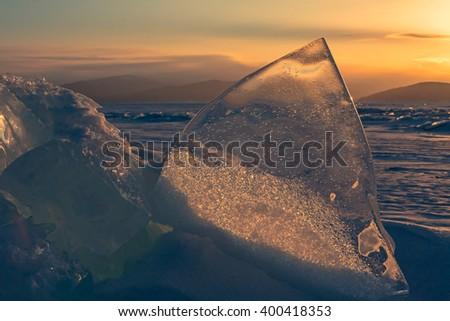 Transparent piece of ice on sunset sky background. - stock photo