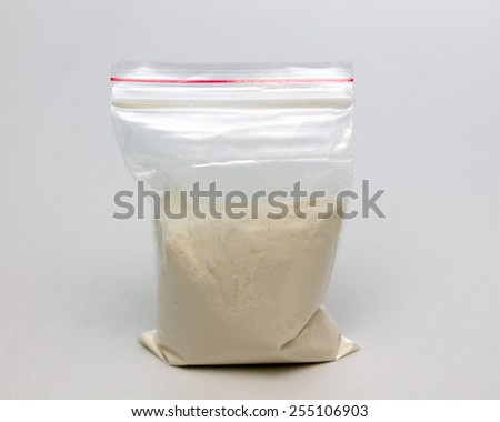 Transparent plastic bags with white powder on a white background - stock photo