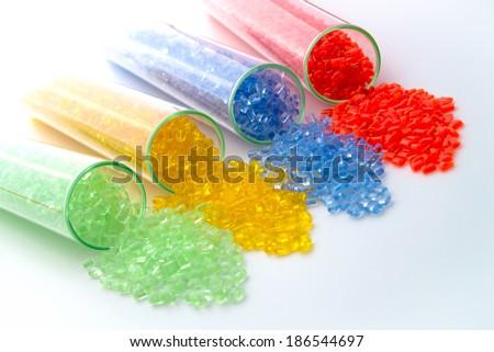 transparent plastic granulates in test-tubes - stock photo