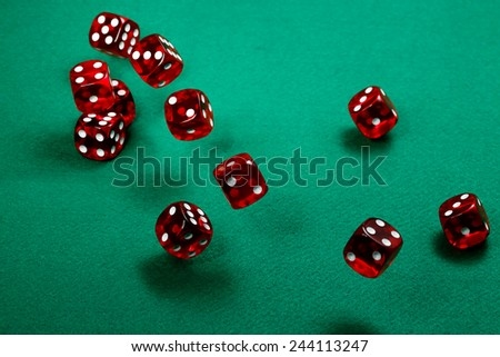 transparent red dice over green felt - stock photo