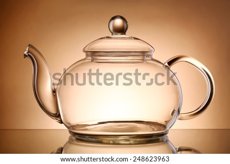 Transparent teapot on gray background - stock photo