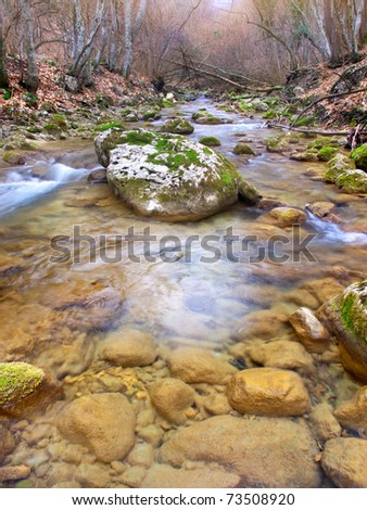 Transparent water in river with yellow stone - stock photo