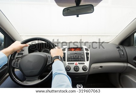 transport, business trip, destination and people concept - close up of young man driving on car parking - stock photo