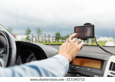 transport, business trip, technology, navigation and people concept - close up of male hand using gps navigator while driving driving car - stock photo