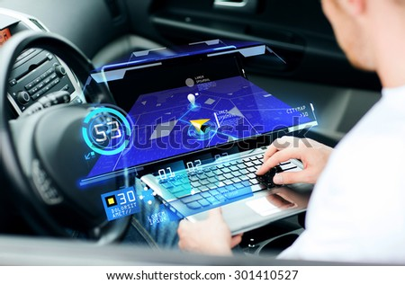 transport, modern technology and people concept - man using navigation system on laptop computer in car - stock photo