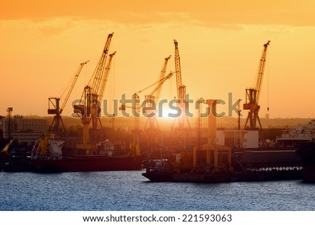 Transportation and logistic background - freight cargo ships and cranes in seaport on sunset - stock photo