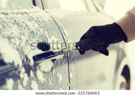 transportation and ownership concept - closeup of man hand opening car with key - stock photo