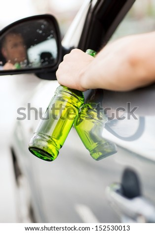 transportation and vehicle concept - man drinking alcohol while driving the car - stock photo