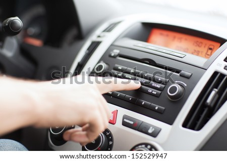transportation and vehicle concept - man using car audio stereo system - stock photo