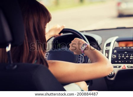 transportation and vehicle concept - woman driving a car and looking at watch - stock photo