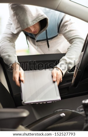 transportation, crime and ownership concept - thief stealing laptop from the car - stock photo