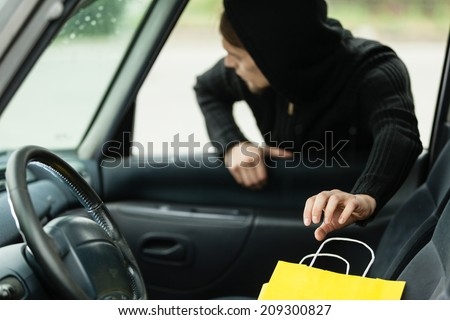 Transportation, crime and ownership concept - thief stealing shopping bag from the car - stock photo