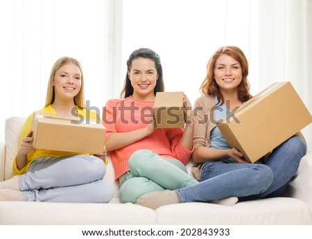transportation, post and friendship concept - three smiling teenage girls with cardboard boxes at home - stock photo