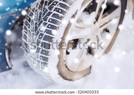 transportation, winter and vehicle concept - closeup of car wheel - stock photo