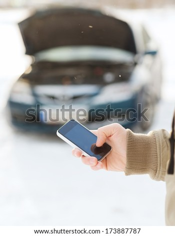 transportation, winter and vehicle concept - closeup of man with broken car and cell phone - stock photo