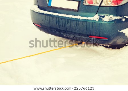 transportation, winter and vehicle concept - closeup of towing car with towing rope - stock photo