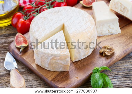 Trappe  cheese on wooden cutting board with cherry tomatoes - stock photo