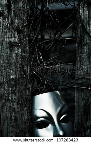 Trapped - Mask behind Weathered Fence - stock photo