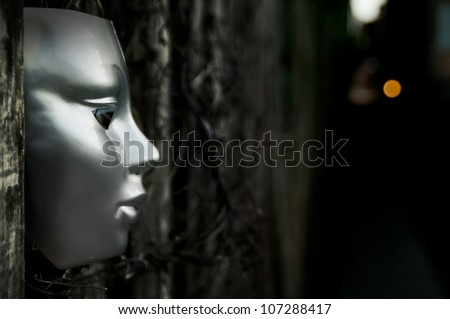 Trapped - Mask on Weathered Fence - stock photo