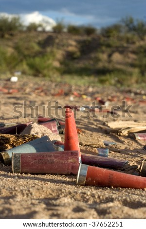 Trash and shotgun shells laying in the dirt - stock photo