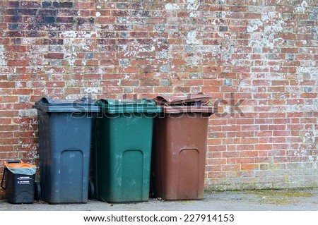 Trash can dustbins outside against brick wall  - stock photo