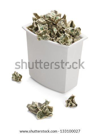 Trash Can full of Crumpled Dollars Over Flowing of Frustration. Isolated on a white background. - stock photo