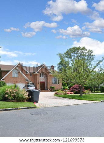 Trash Day Suburban Neighborhood Large Brick McMansion Style Architecture Home Sunny Blue Sky Day Clouds - stock photo