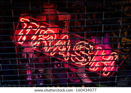 Trash fluorescent red neon sign inside a shop with metal grid on the front - stock photo
