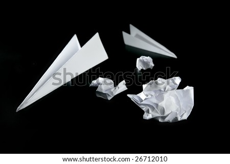Trash paper and air plane, bored in the office metaphor, over black - stock photo
