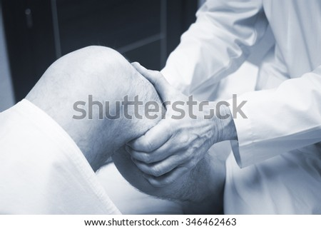 Traumatologist orthopedic surgeon doctor examining middle aged man patient to determine injury, pain, mobility and to diagnose medical treatment in leg, knee meniscus cartilage, ankle and foot injury - stock photo