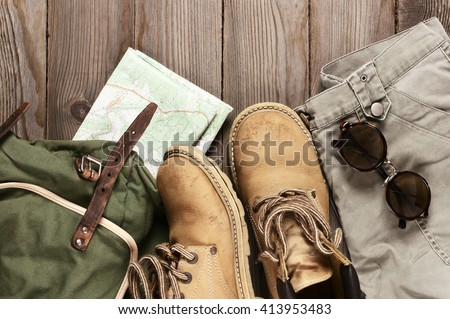 Travel accessories set on wooden background: old hiking leather boots, pants, backpack, map and sunglasses. Top view point. - stock photo