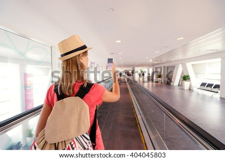 Travel and cell connection. Young woman using smartphone while walking on airport terminal transporter. - stock photo