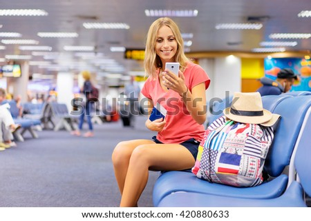 Travel and technology. Pretty young woman using smartphone and holding tickets while sitting in airport terminal waiting for boarding. - stock photo
