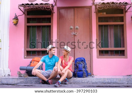 Travel and tourism. Couple of backpackers sitting together on asian street. - stock photo