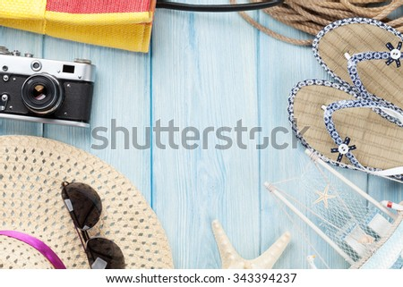 Travel and vacation items on wooden table. Top view with copy space - stock photo