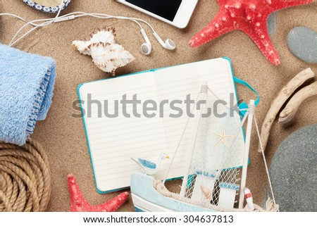 Travel and vacation notepad with items over sea sand. Top view with copy space - stock photo