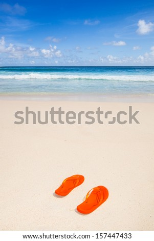 travel background with a pair of orange flip-flops in the sand of a beautiful beach, blue sky and turquoise sea - stock photo