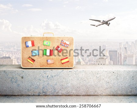 travel bag with many flags and airplane in sky - stock photo